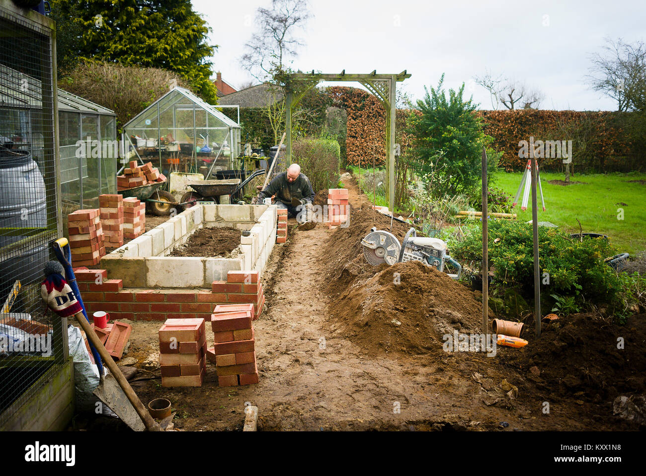 Builder constructing a replacement raised planter from blocks and bricks in late winter in UK - Stock Image