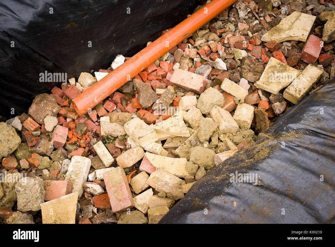 A newly dug pit filled with brick and stone rubble to form a rainwater soakawy from building foundations in UK Stock Photo