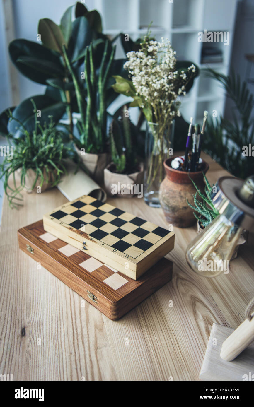 Studio workplace with chess boards, artistic work tools and green plants  - Stock Image