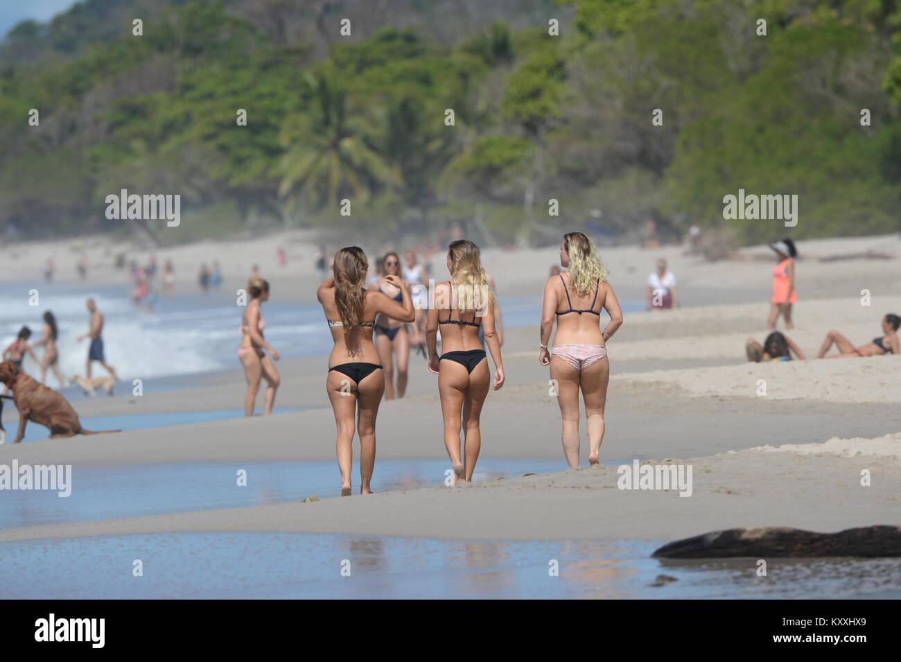 Three girls in bikinis walk along the beach  at Santa Teresa, Costa Rica lifestyle Stock Photo