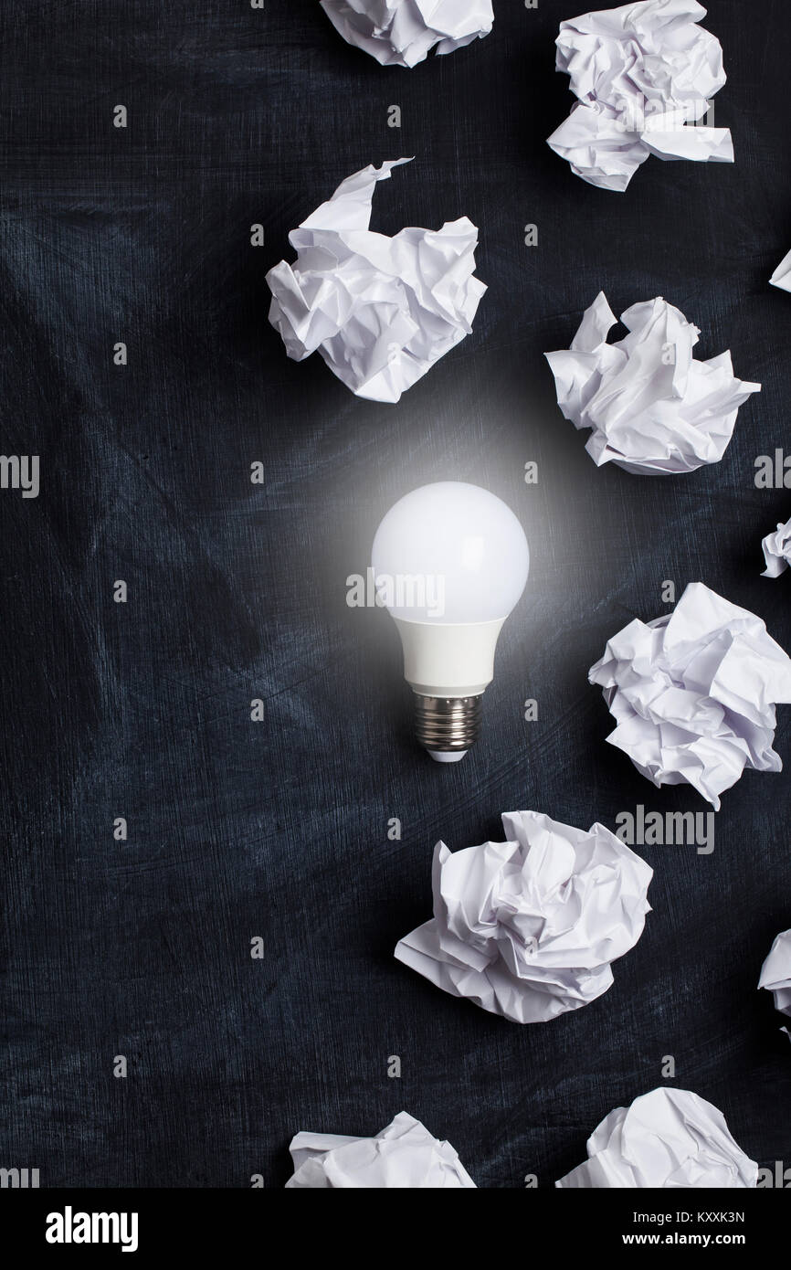 Inspiration and imagination concept. lightbulb with white crumpled paper documents - Stock Image