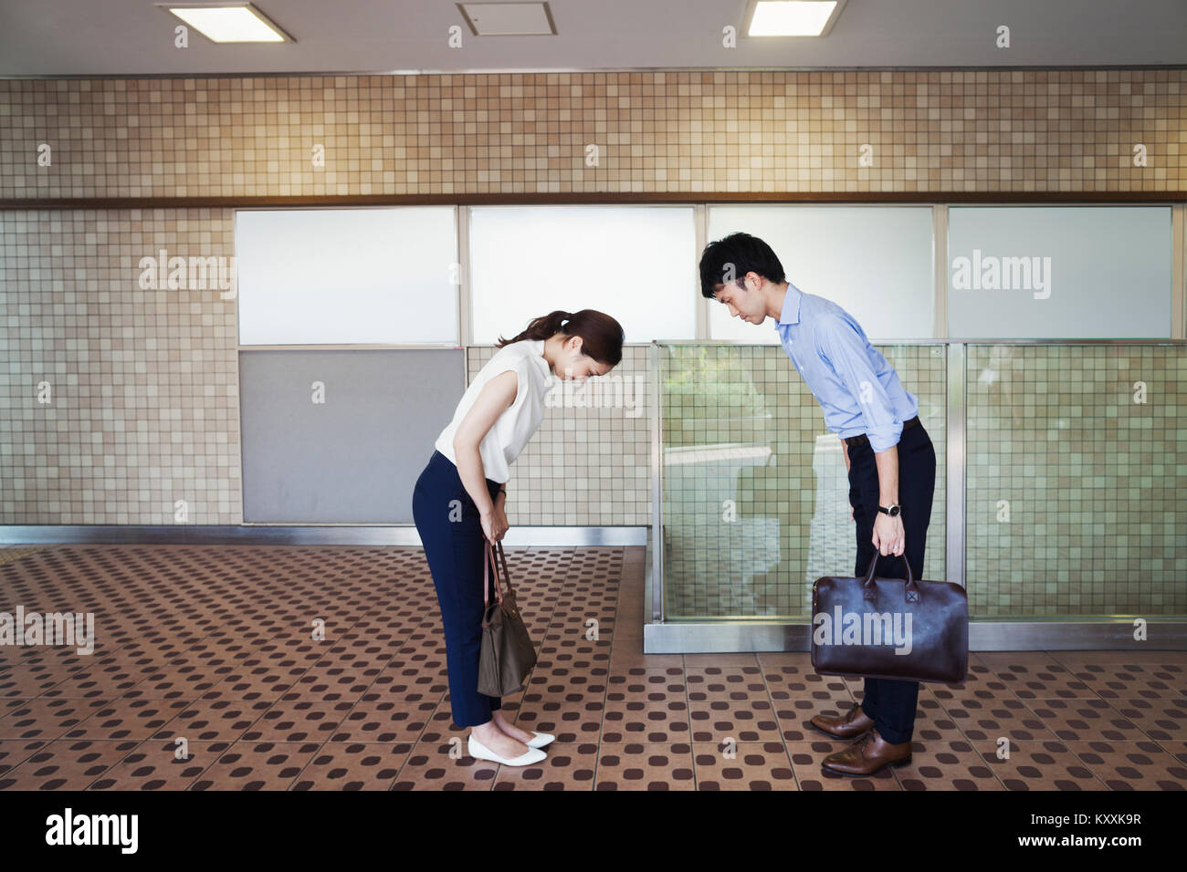 Two people greeting, a man and young woman bowing from the waist when they meet in a subway. - Stock Image