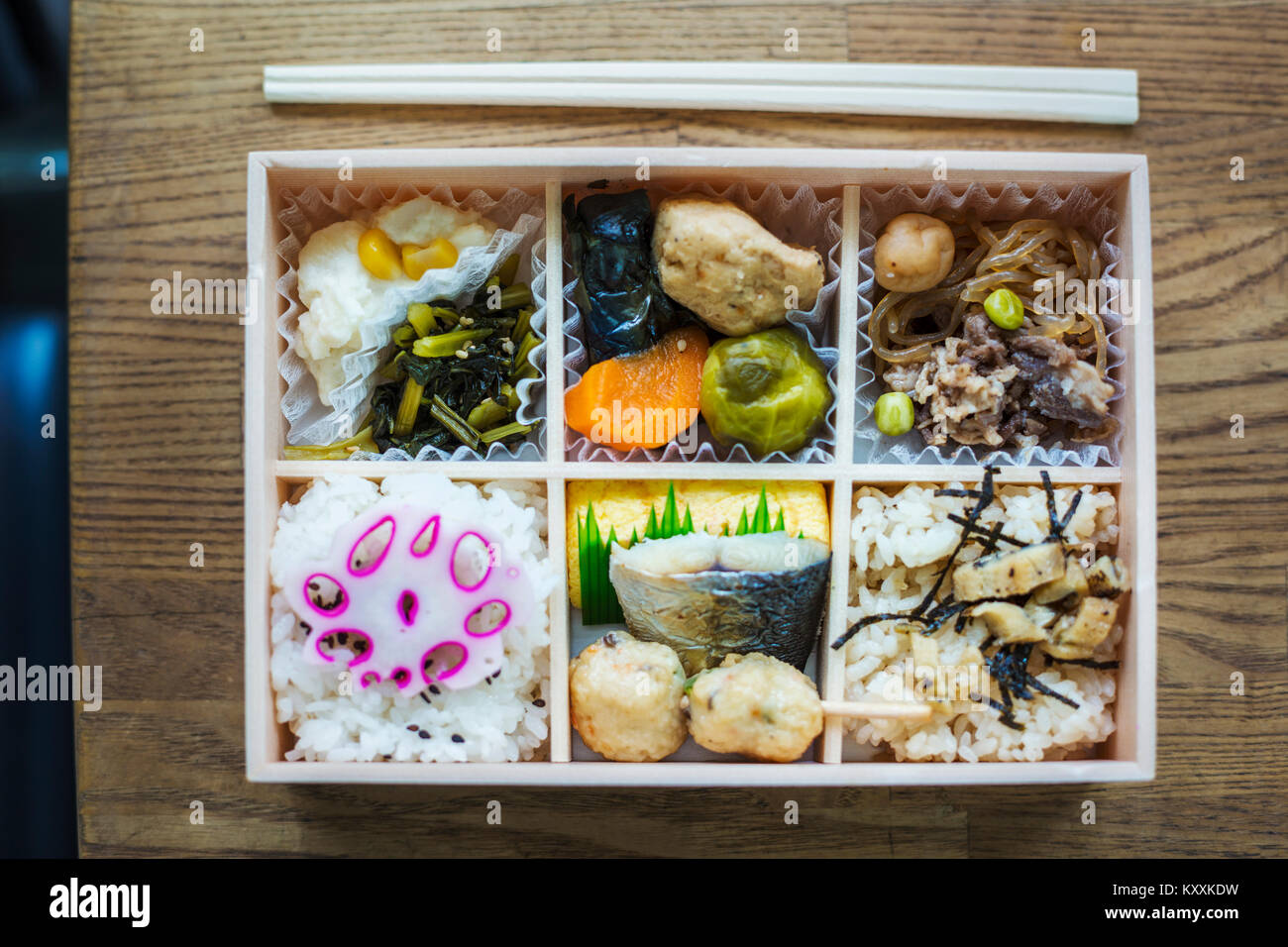 High angle close up of Bento box with traditional Japanese foods and chopsticks on a wooden table. - Stock Image