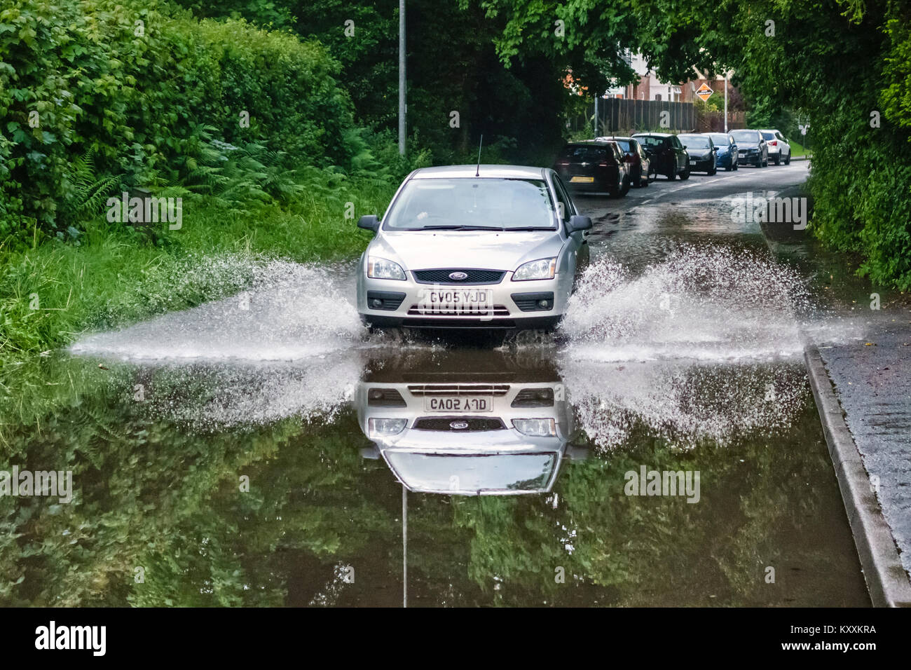 Presteigne, Powys, Wales, UK. A car crossing a flooded stretch of road, the flooding caused by sudden heavy rain - Stock Image