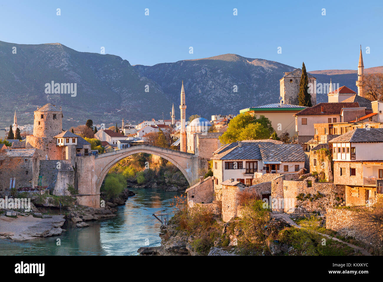 Skyline of Mostar with the Mostar Bridge, houses and minarets, at the sunset in Bosnia and Herzegovina. - Stock Image