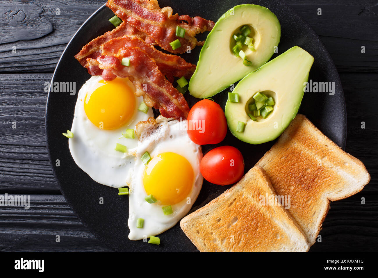 Delicious breakfast of eggs with crispy bacon, avocado, toast and tomatoes close-up on a black plate on the table. Stock Photo