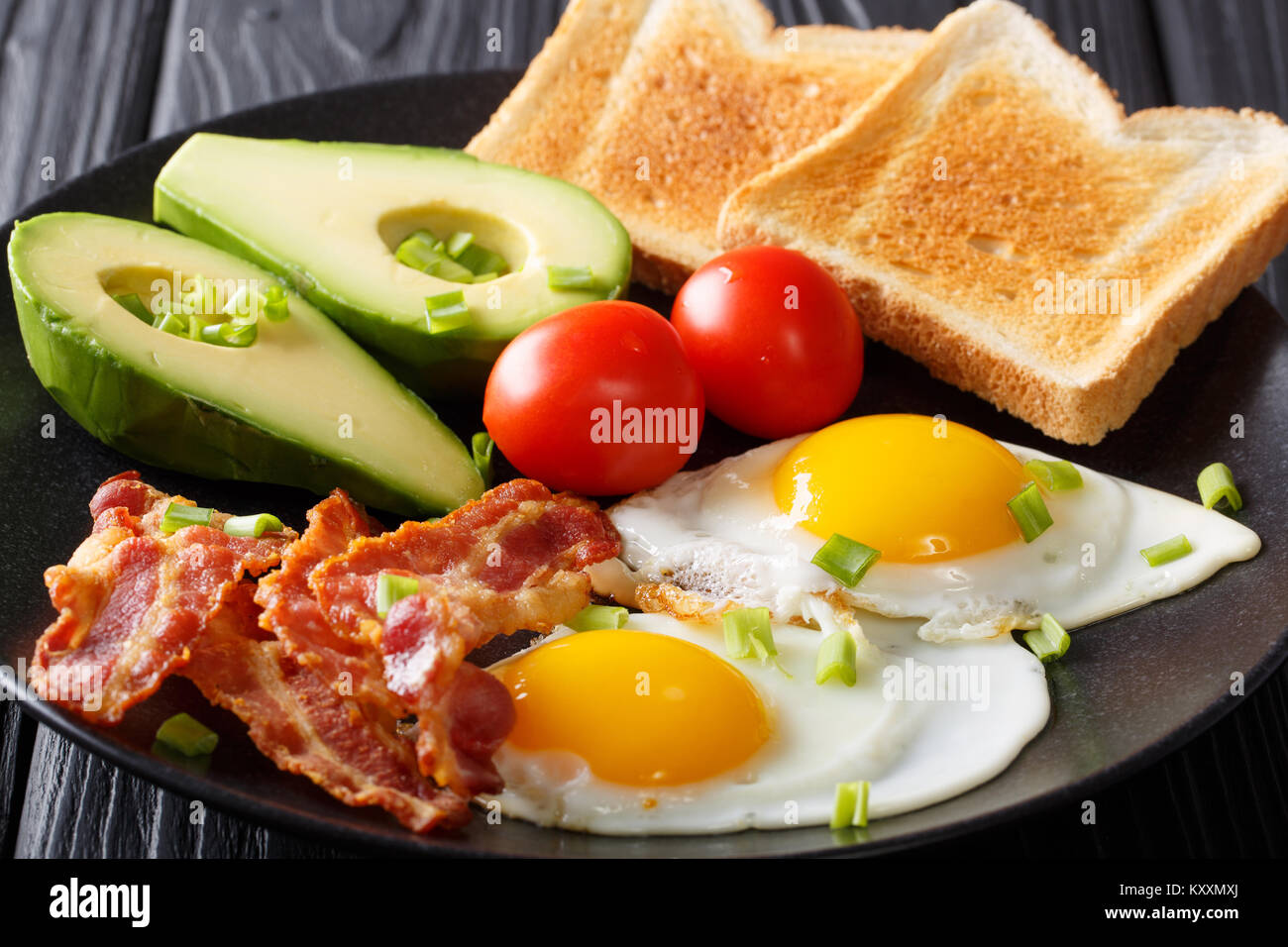 hearty breakfast: fried eggs with bacon, avocado, toast and tomatoes close-up on a plate on a table. horizontal - Stock Image