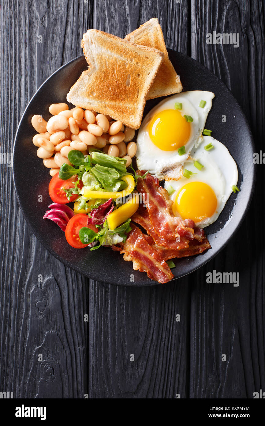 Delicious fried eggs, bacon, beans, toast and fresh vegetable salad on a plate on the table. Vertical top view from Stock Photo