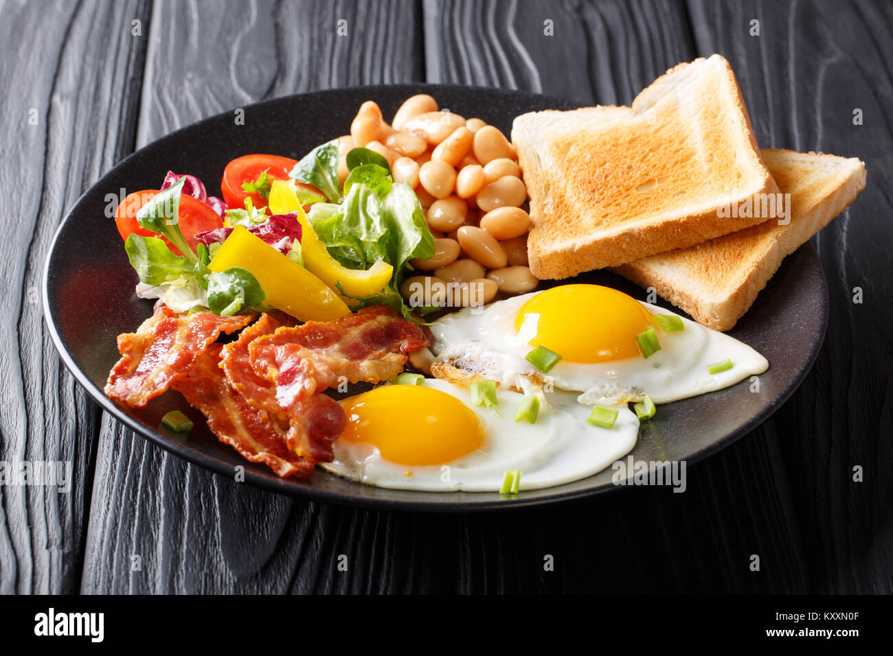 Delicious and hearty meal: two fried eggs with bacon, beans, toast and vegetable salad on the table. Classic breakfast. - Stock Image