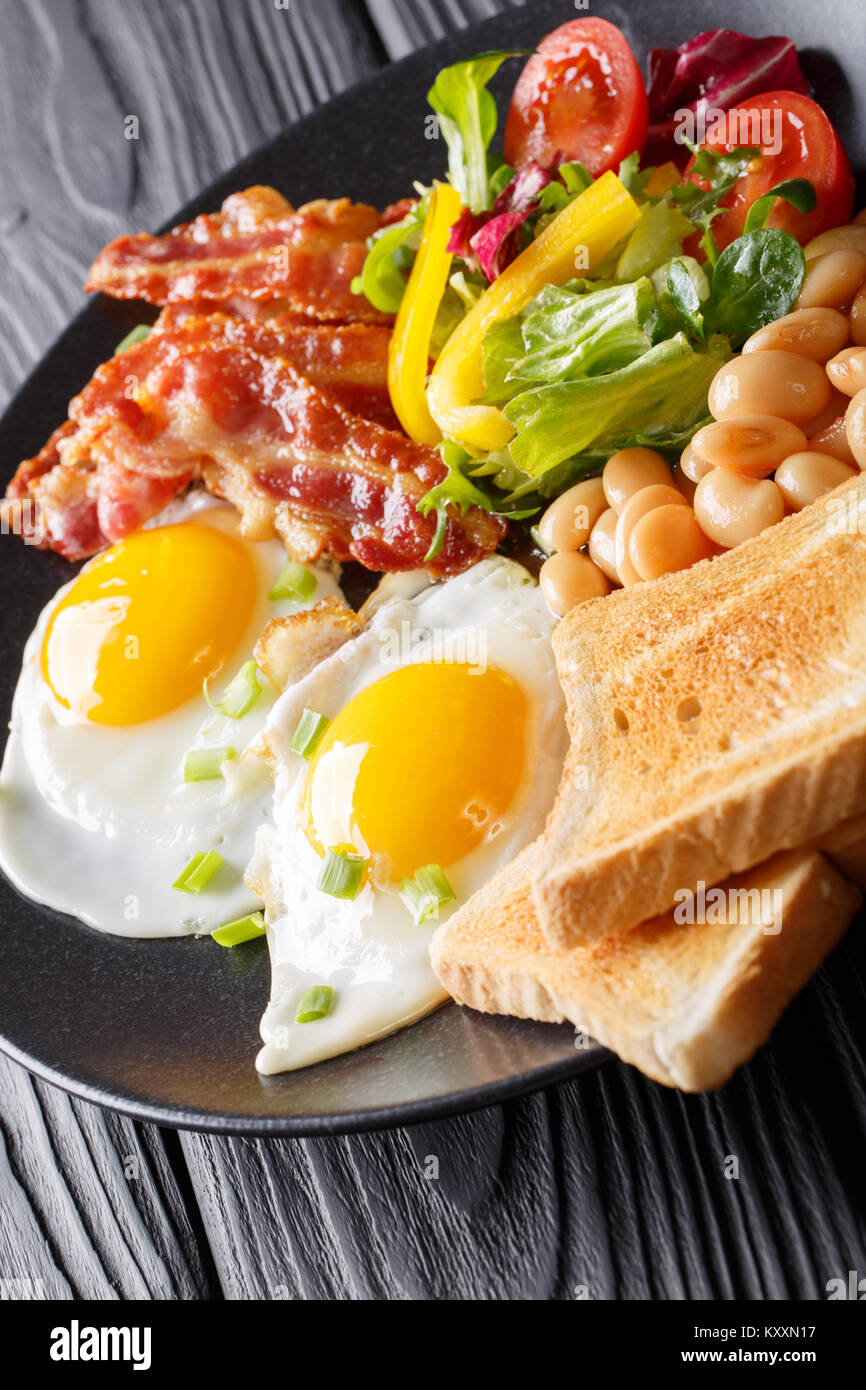hearty breakfast: fried eggs with bacon, beans, toast and fresh vegetable salad on a plate on the table. vertical - Stock Image