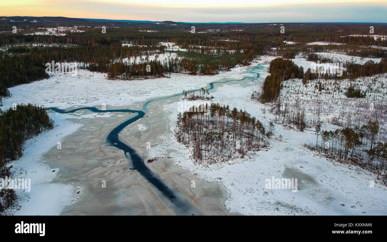 Ice breaking on a lake during sunset in a swedish forest. Photographed by drone during the winter. - Stock Image