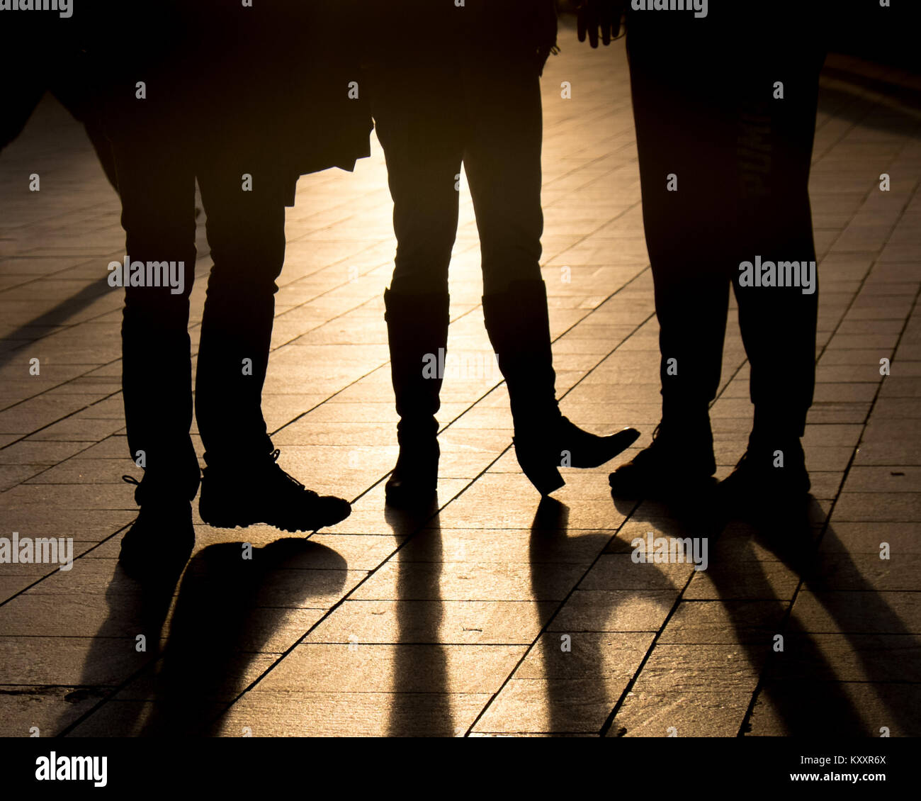 Friends stood chatting at sunset. - Stock Image