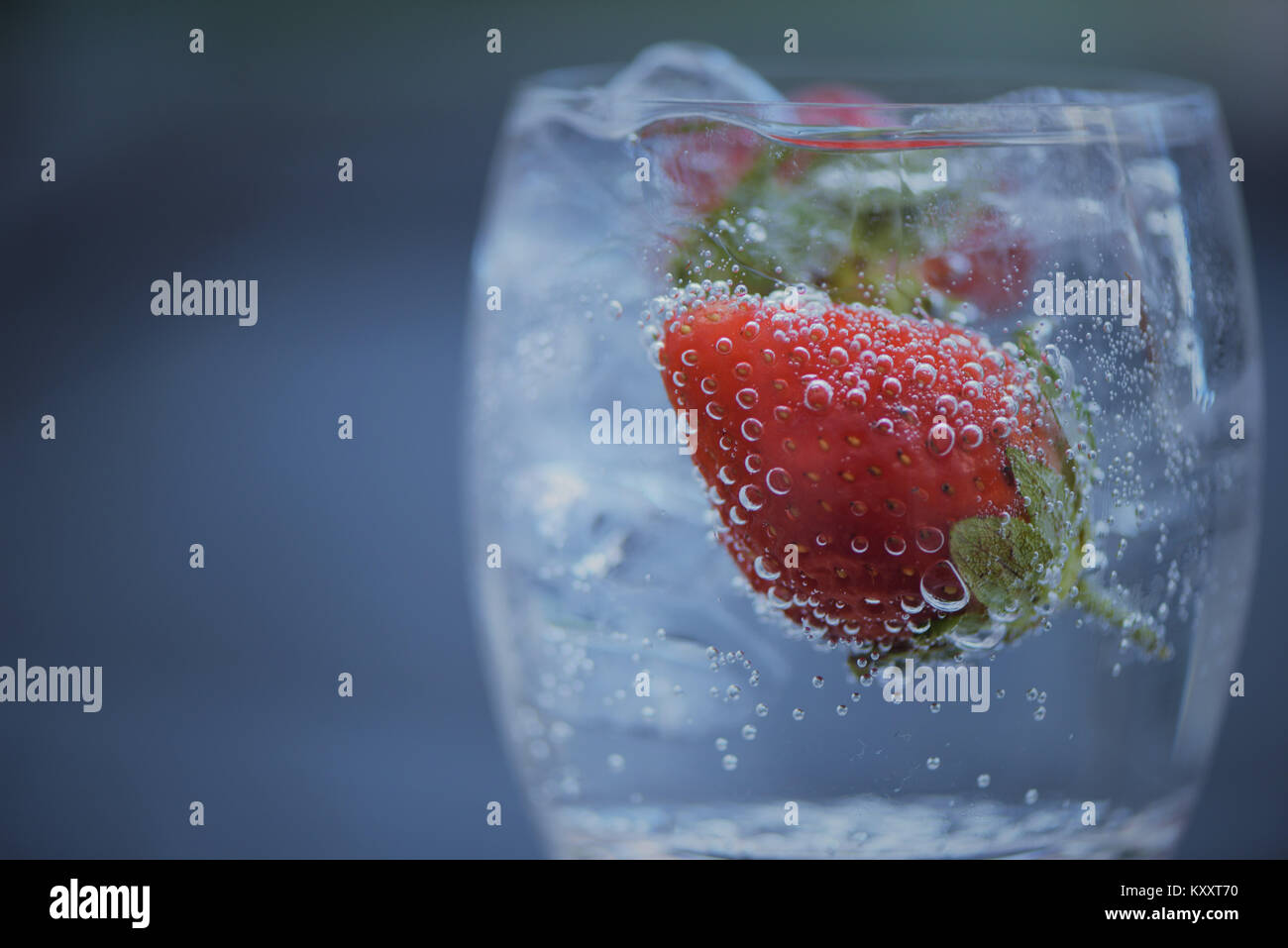 refreshing food and drink macro close up photography image of red fruit strawberry in a glass of ice cubes and sparkling - Stock Image