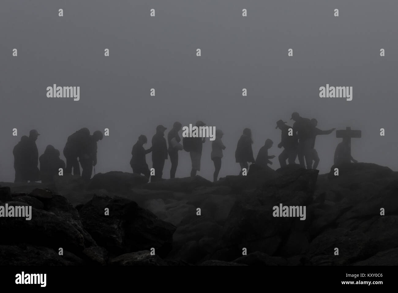 Bad fog & weather as hikers summit Mt. Washington in New Hampshire - White Mountain National Forest -  extreme conditions Stock Photo