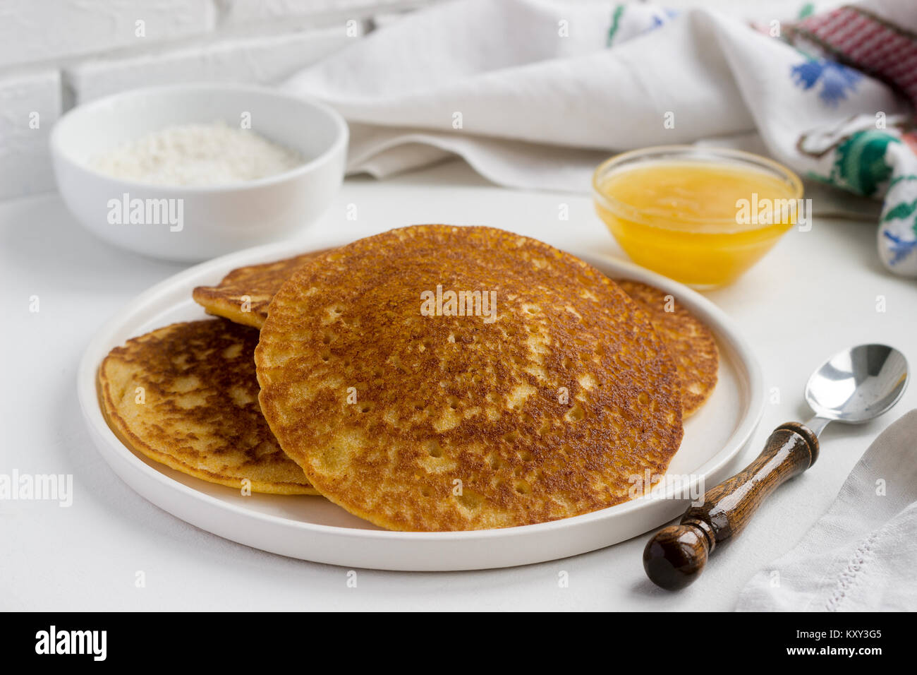 Coconut corn pancakes with honey. Rustic style. - Stock Image