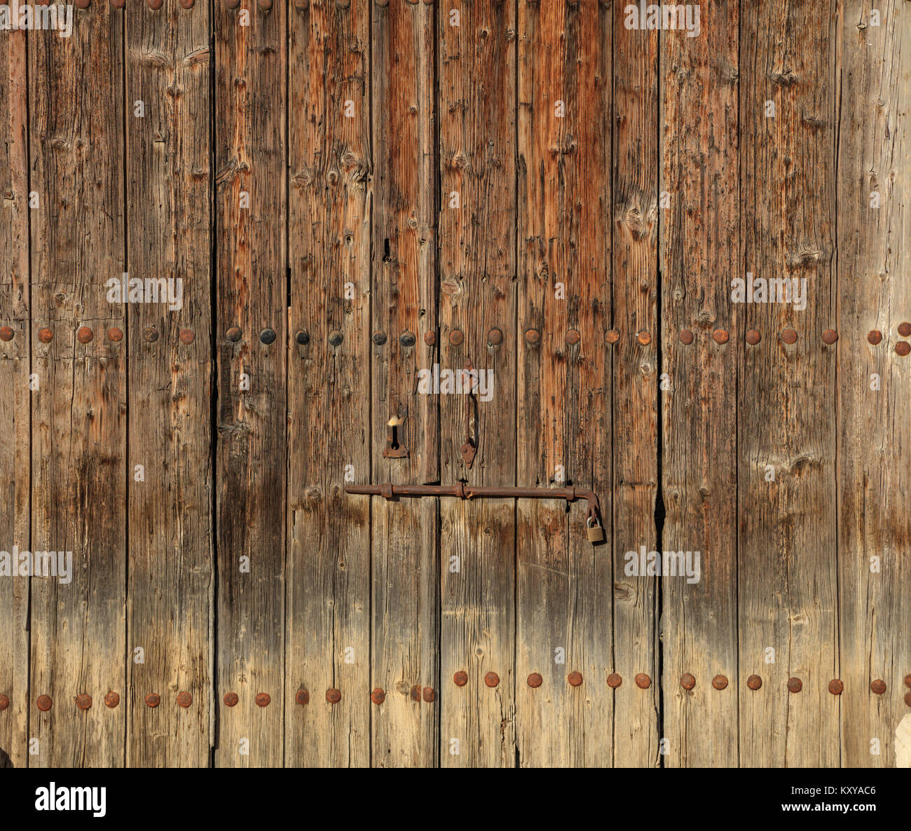 Wooden brown door. Timeworn background with rusty latch and padlock. Close up view with details. - Stock Image