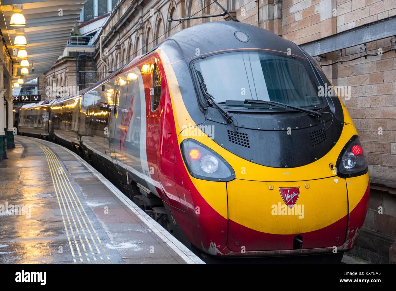 Virgin Trains Pendolino locomotive to London Euston  on West Coast Main line  at platform at Waverley Station in Stock Photo