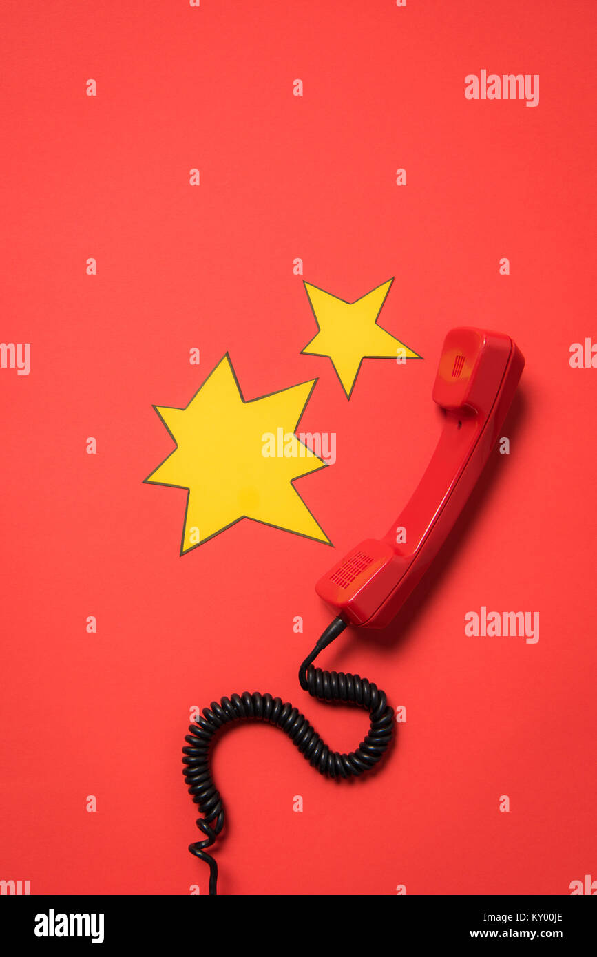 Traditional telephone receiver and blank star shaped speech bubbles isolated on red - Stock Image