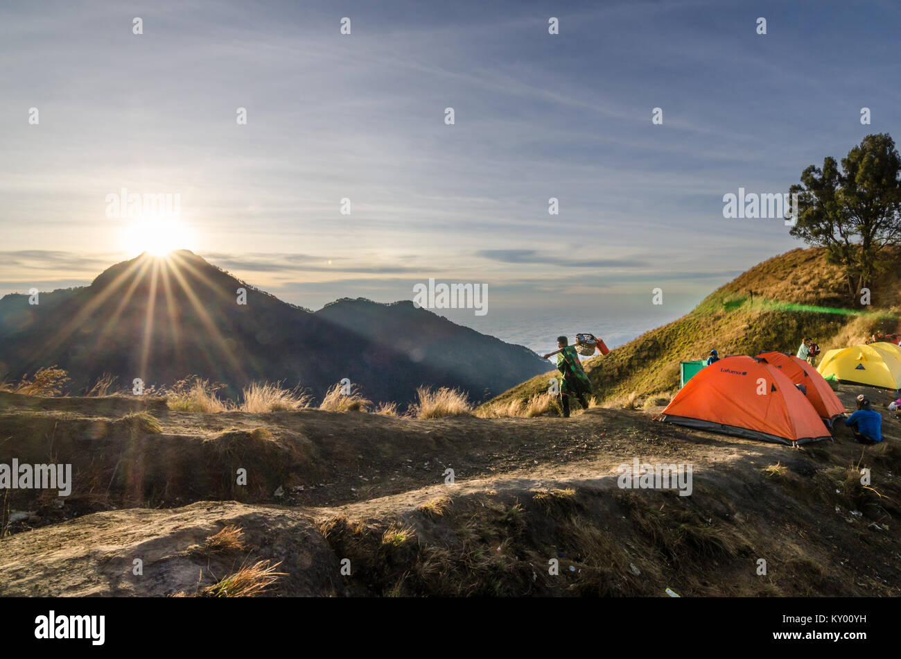 Porter of Mount. Rinjani helping hiker to carry stuff. The mountain is the second highest volcano in Indonesia and - Stock Image