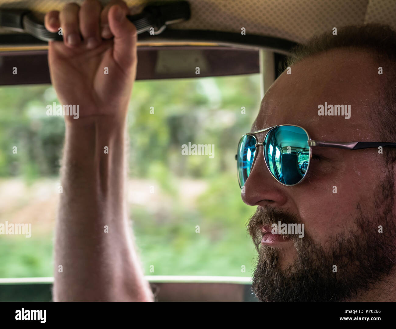 Headshot of man wearing sunglasses,  riding in a car, sweating, and holding onto grip handle. - Stock Image