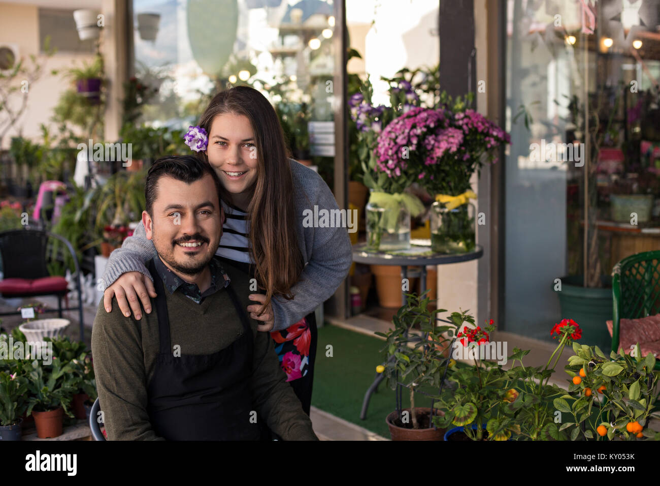 Smiling florist couple in a flower shop. Male wearing black apron sitting in a chair and smiling female with a lisianthus - Stock Image