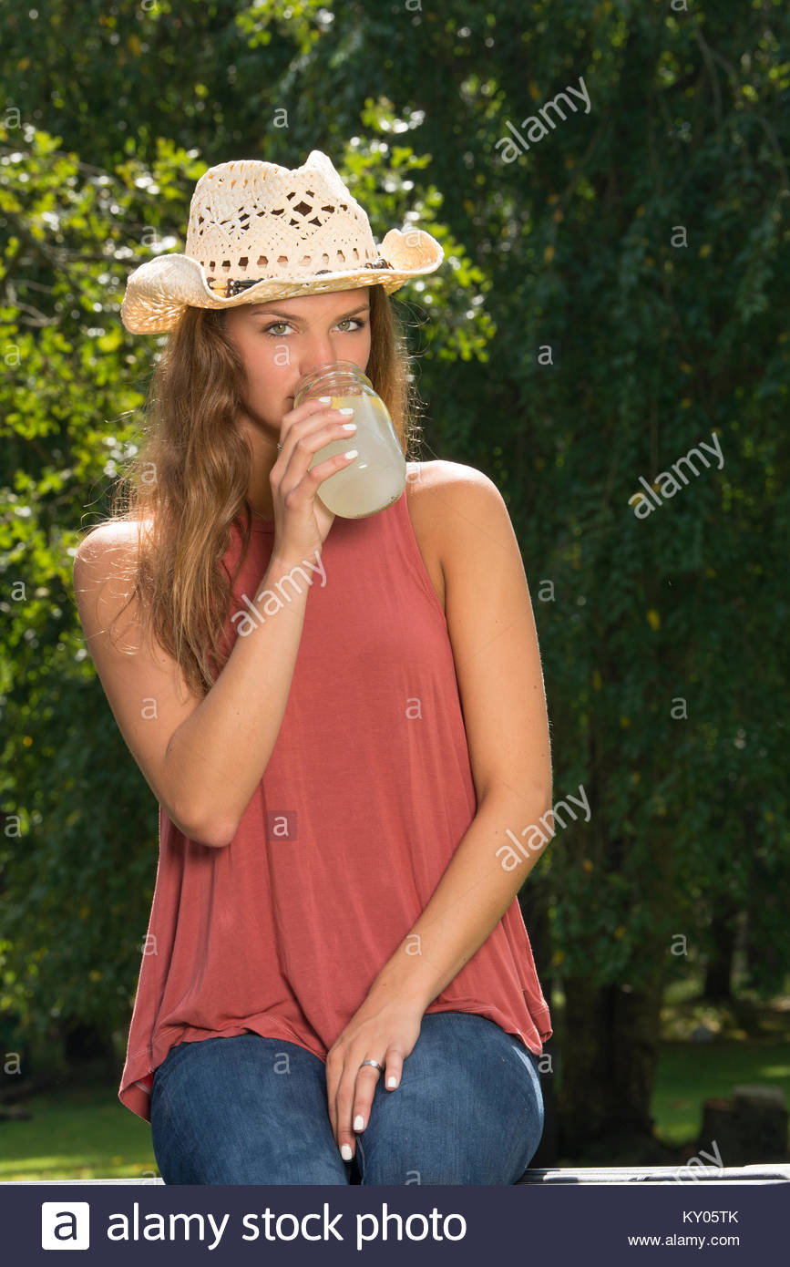 6e7b9cf7bea Beautiful young country girl sipping from a jar of lemonade in back of  pickup truck on