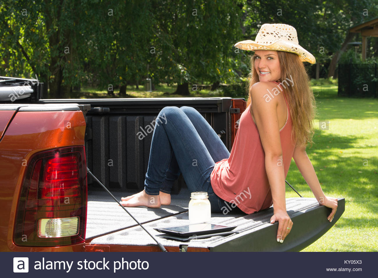 66cea0bb078 Beautiful young country girl poses with jar of lemonade in back of pickup  truck on farm