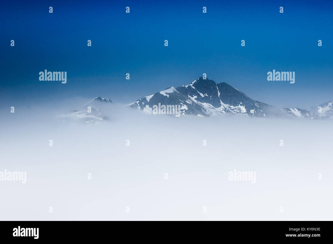 The Scottish mountain Ciste Dubh (The Black Coffin) rearing up impressively through a cloud inversion at the end - Stock Image