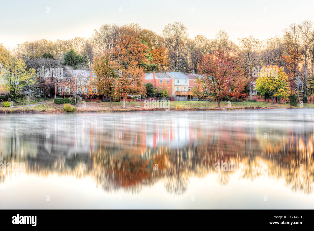 Sunrise on Braddock lake in Burke, Virginia, USA, Fairfax county with reflection of townhouses, fog, mist on water - Stock Image