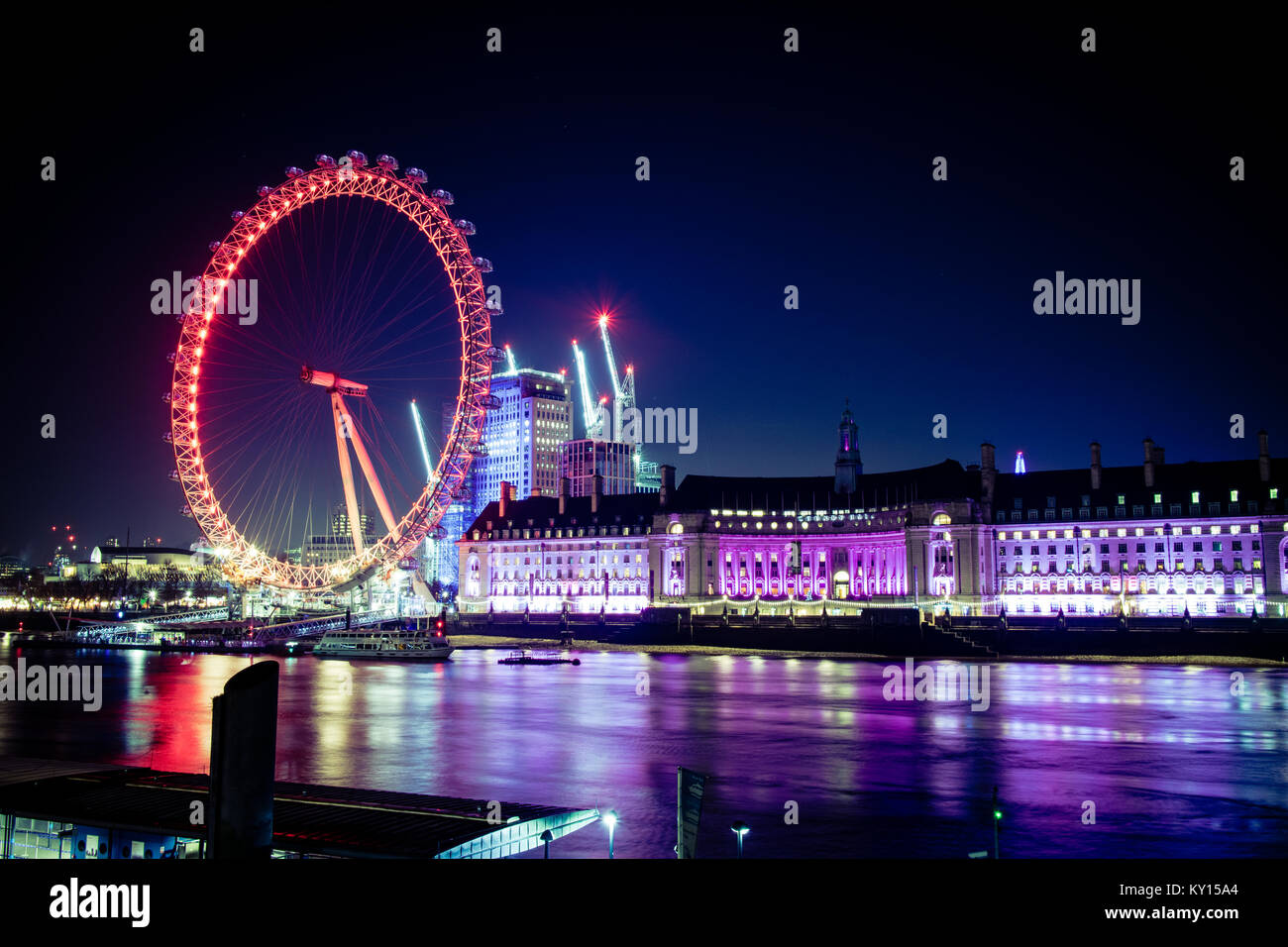 The London eye and the Thames river lit up at night. - Stock Image