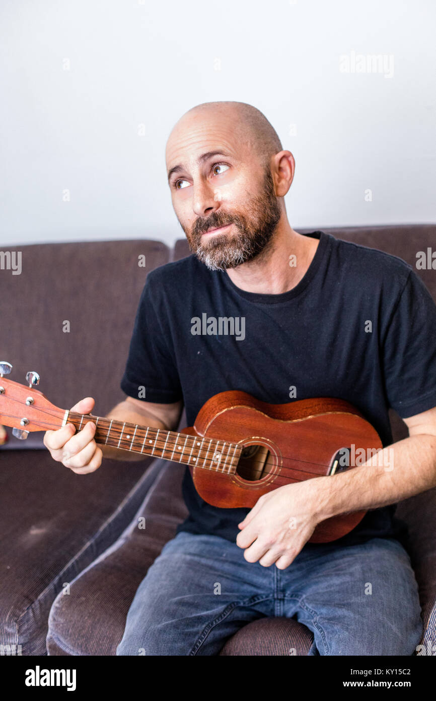 BALD MAN WITH BEARD PLAYS LEFT HANDED UKULELE. SCHULTZ THE PUPPET OVER HIS RIGHT SHOULDER AND ELEVEN YEAR OLD BOY - Stock Image