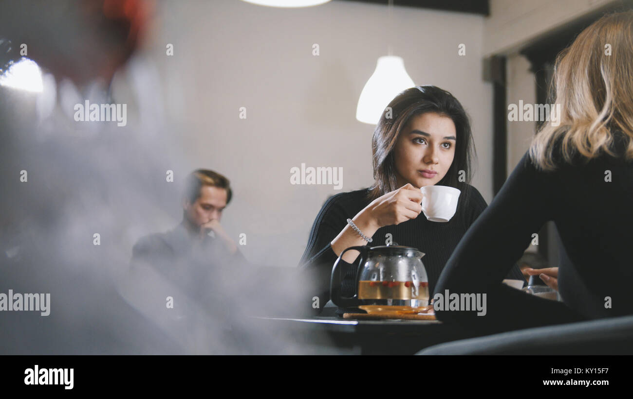 Pretty young woman drinking coffee and smiling in the cafe - Stock Image