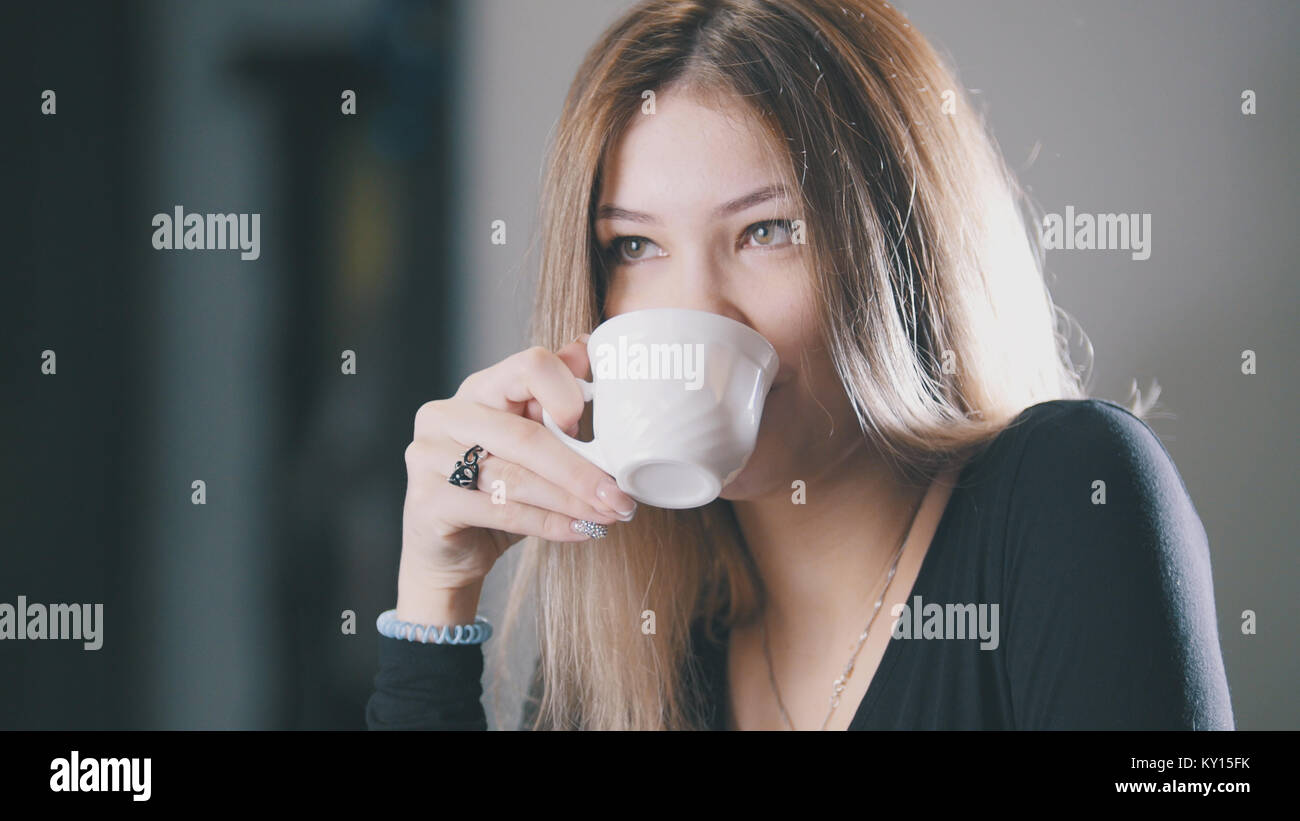 Pretty blonde young woman drinking coffee and smiling in the cafe - Stock Image