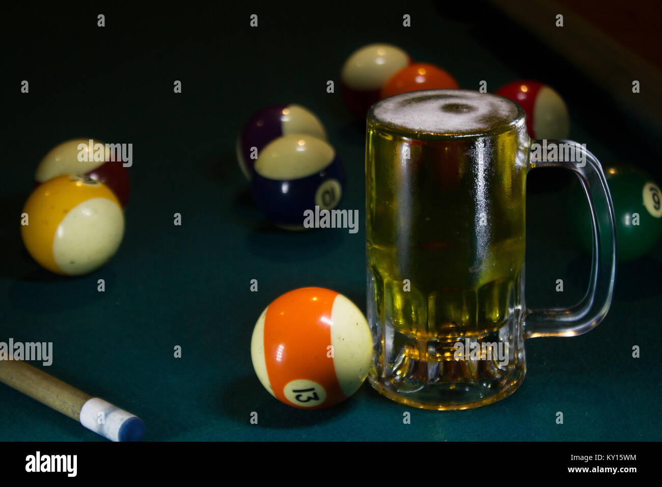 cold beer mug on a green billiard table with several colorful billiard balls and cue stick - Stock Image