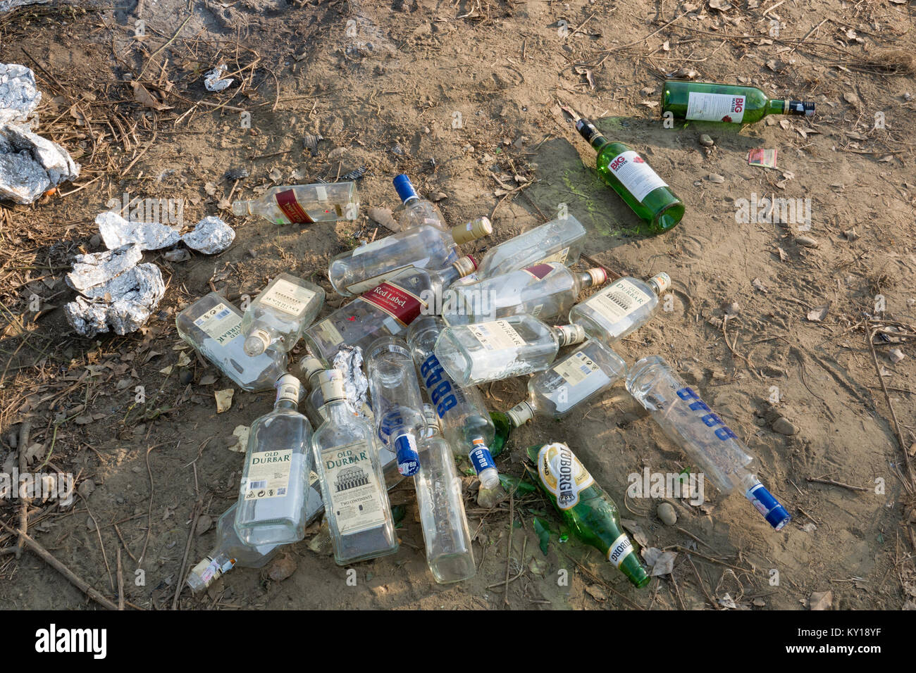 Discarded empty alcohol spirits bottles and other trash left in park - Stock Image