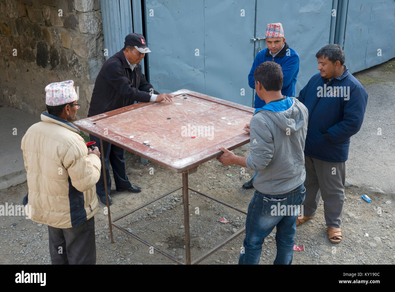 Men playing game of carrom in street in Pokhara, Nepal - Stock Image
