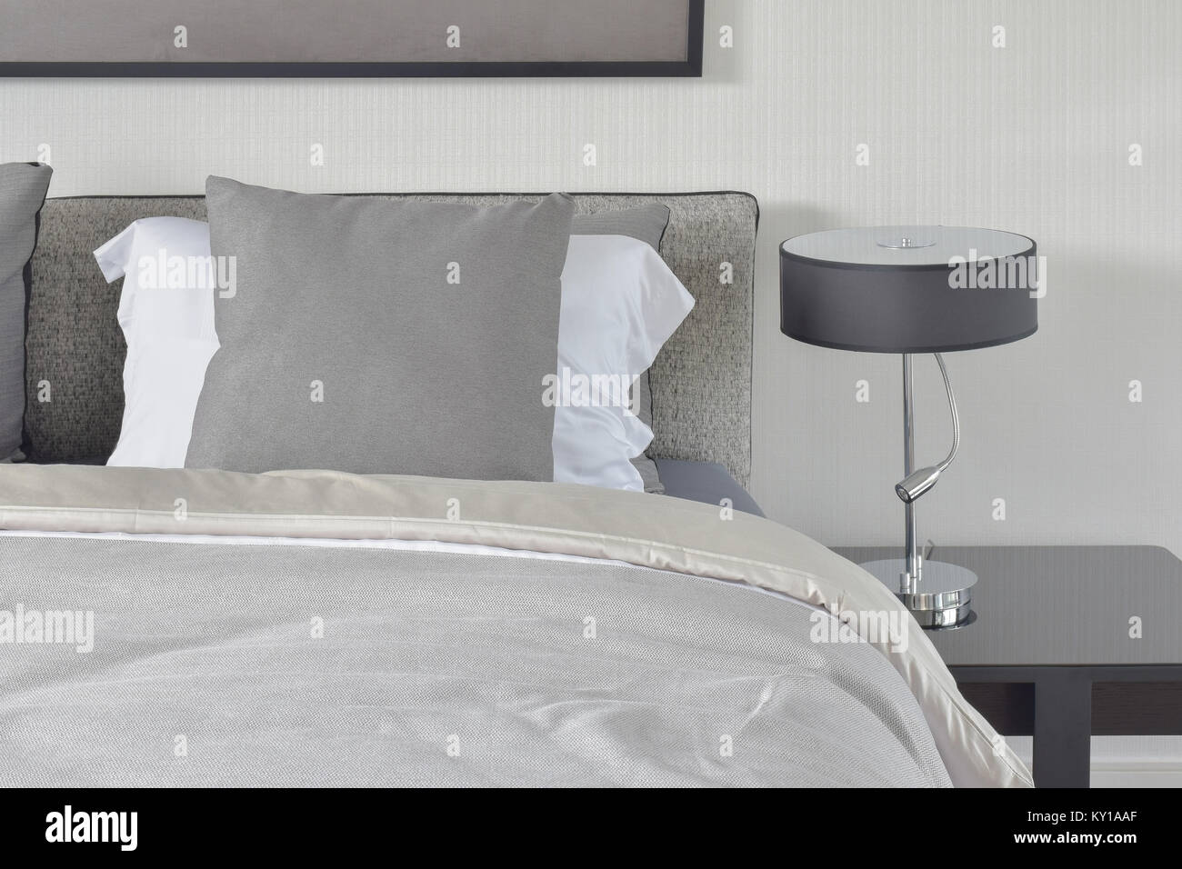 Dark gray pillow with comfy bed and black shade reading lamp - Stock Image