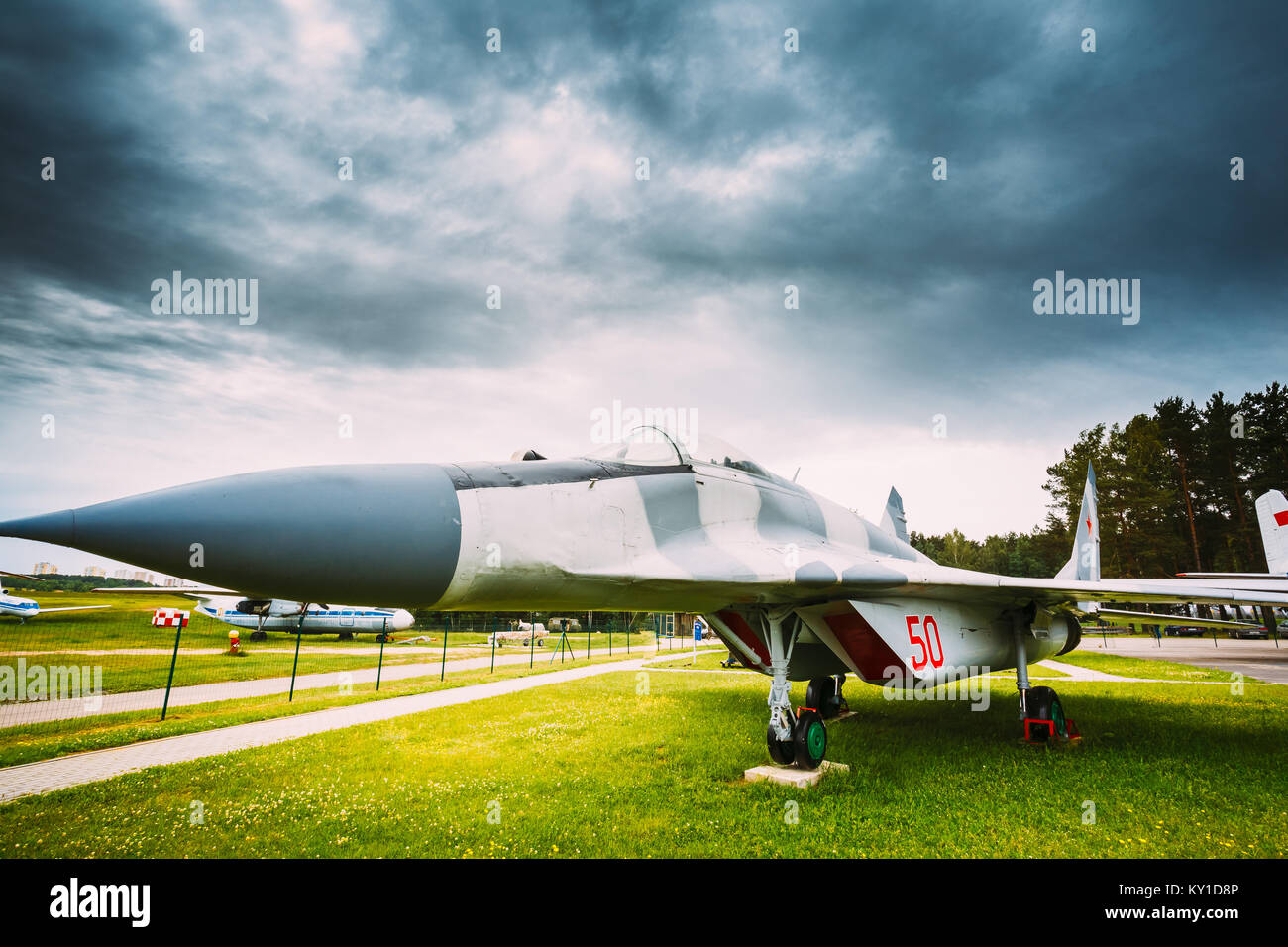Russian Soviet Military Plane Aircraft multipurpose frontline fighter Stands In Grass At Aerodrome. Stock Photo