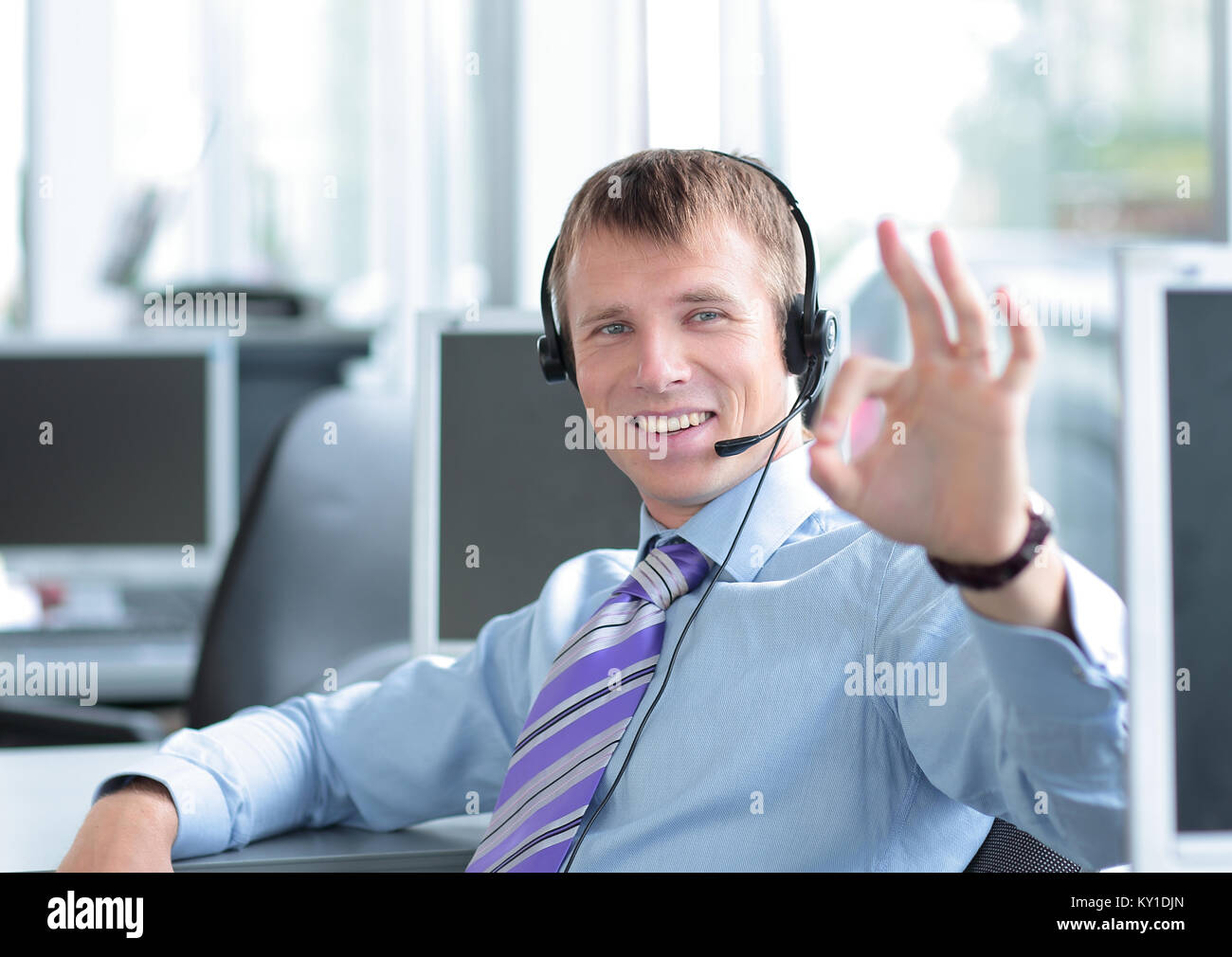 Happy young business man in headset working on computer. Stock Photo