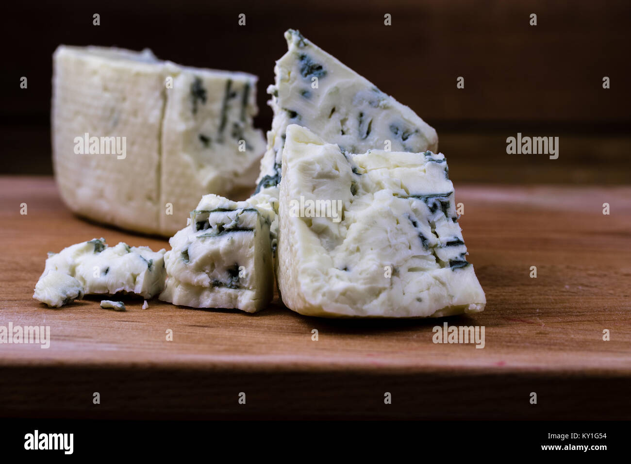 Danish blue or roquefort cheese macro shot on the cutting board with coarse edges and moldy veins exposed. - Stock Image