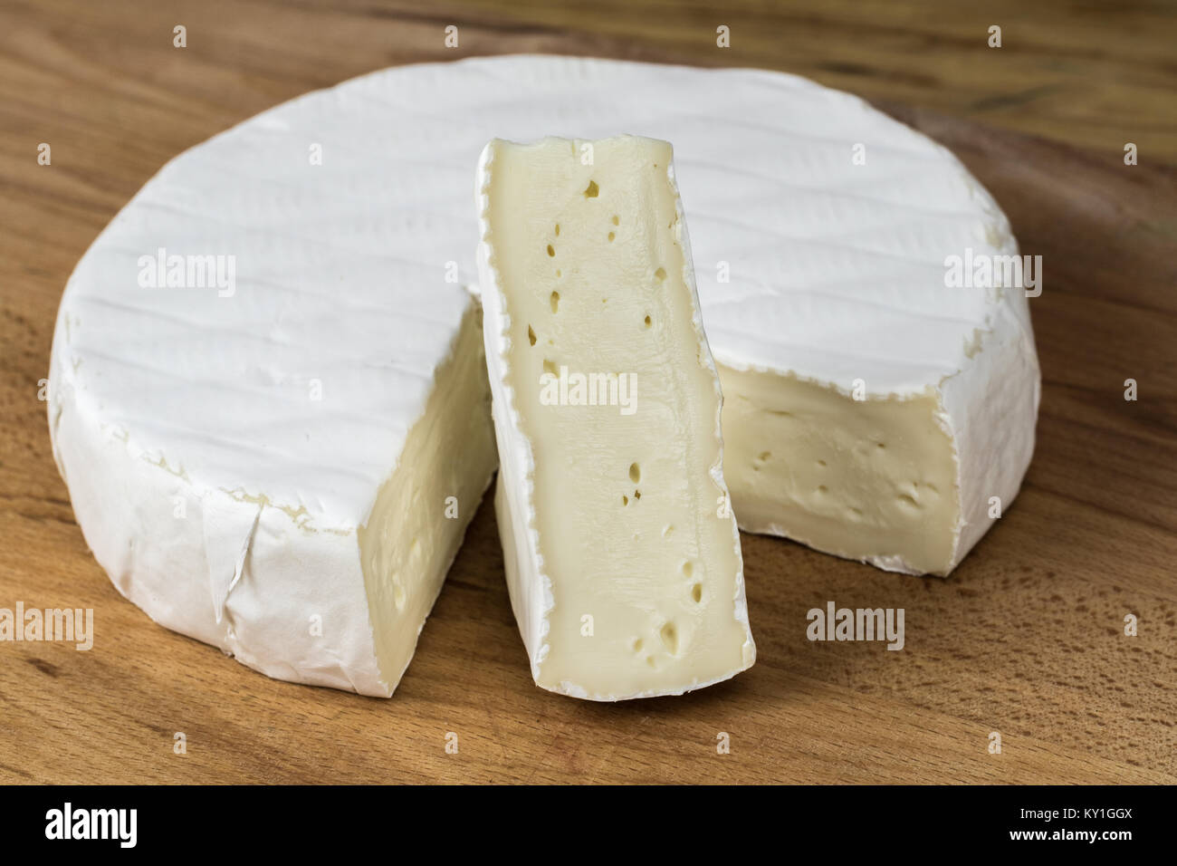 Camembert cheese brie.Triangle cut-out placed vertically. - Stock Image