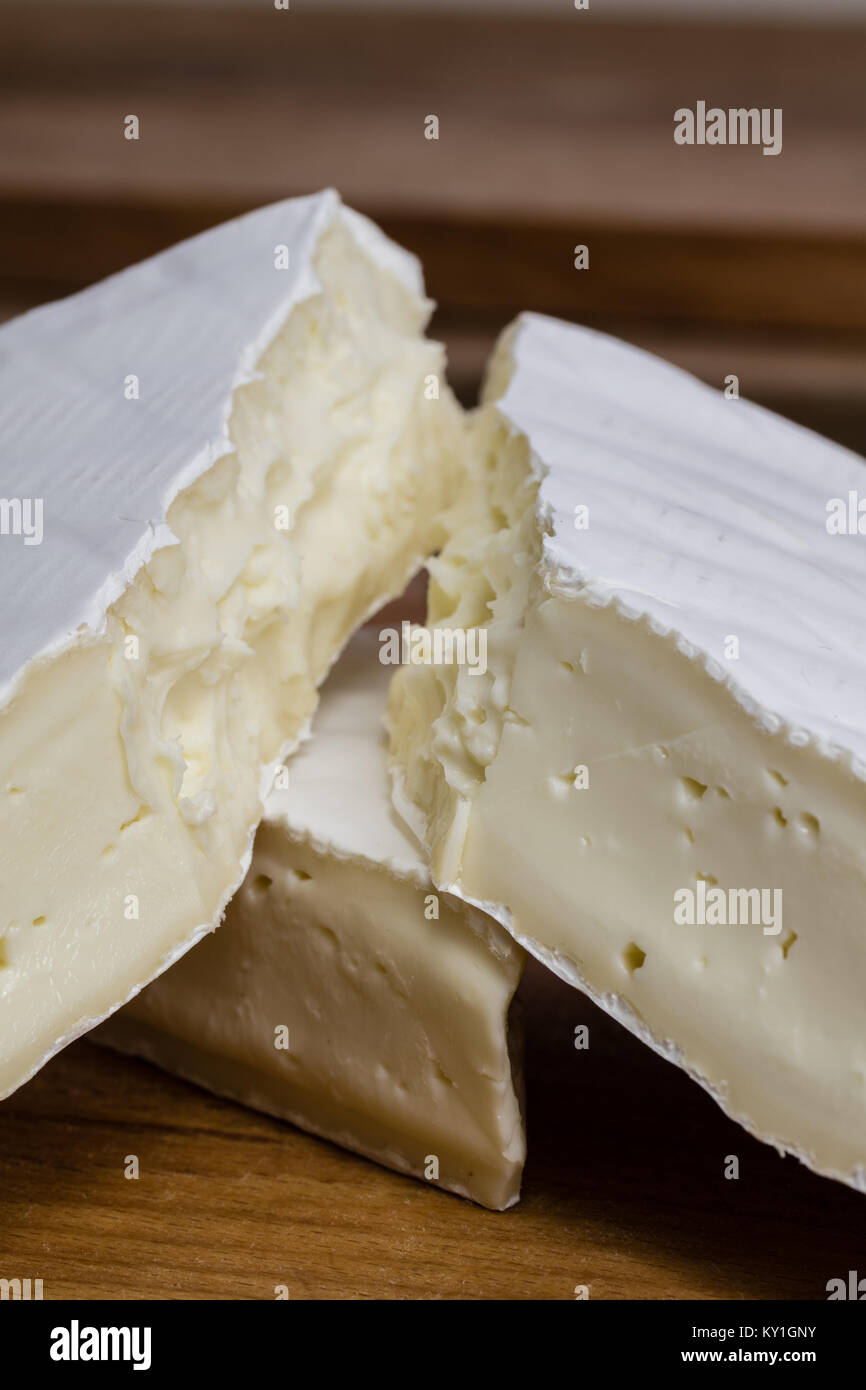 Close up of Camembert cheese. Brie with coarse edge broken into pieces cremy and delicious. - Stock Image