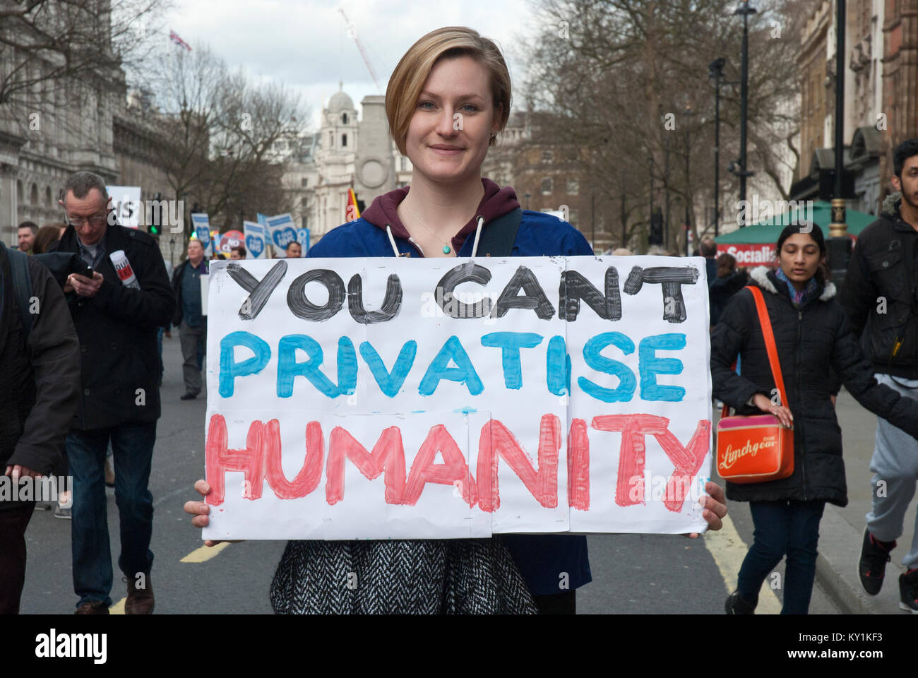 Demonstration in support of NHS, a smiling young woman carrying poster 'You can't privatise humanity' - Stock Image