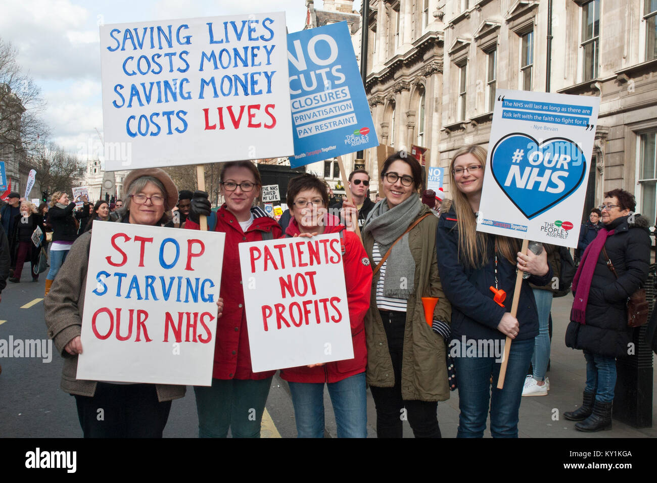 lively demonstration with five smiling women with placards ''Stop starving our NHS' 'Patients not - Stock Image