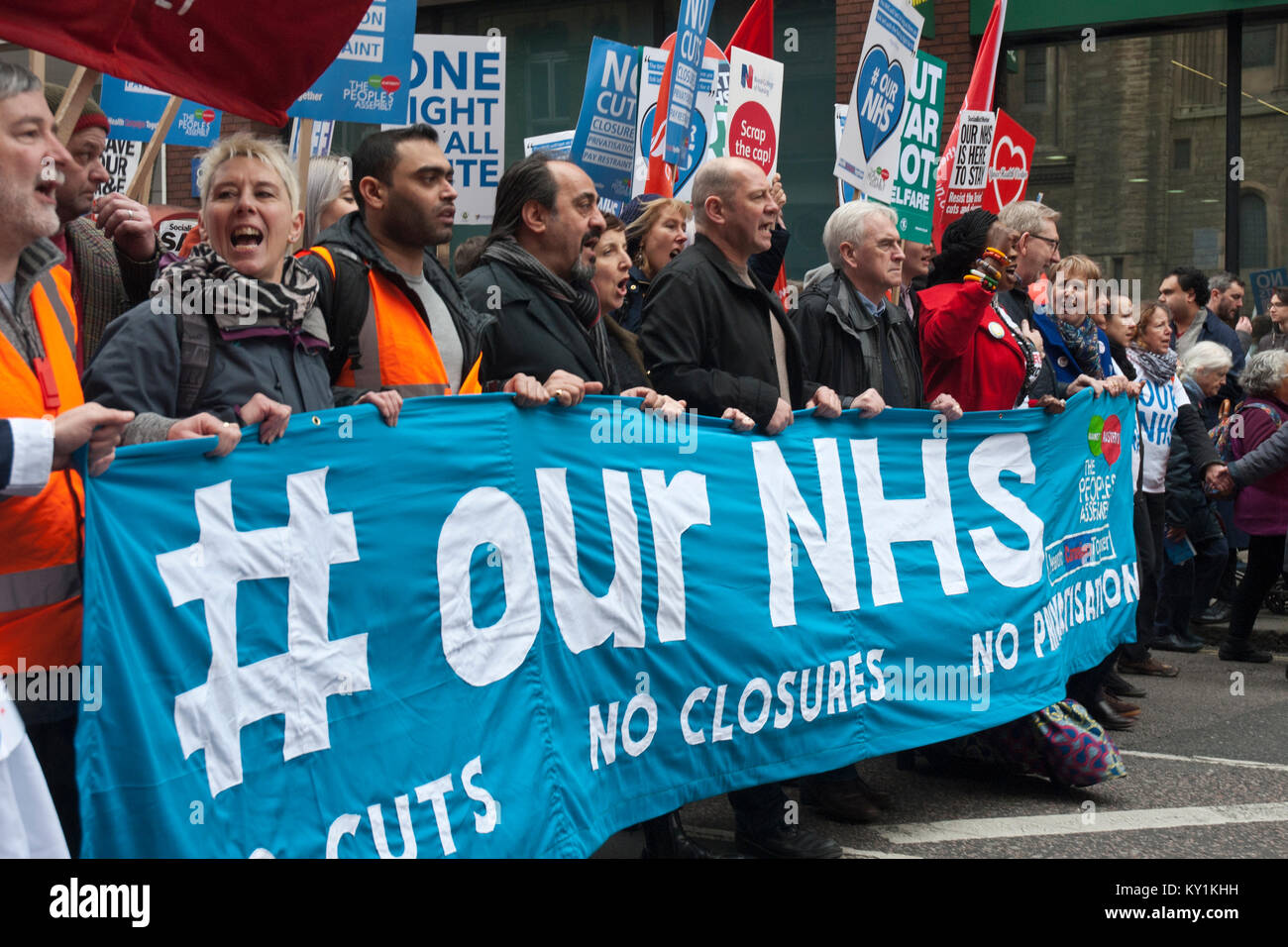 Lead banner of demonstration 'Our NHS', colourful with many people and placards with John McDonald, shadow - Stock Image