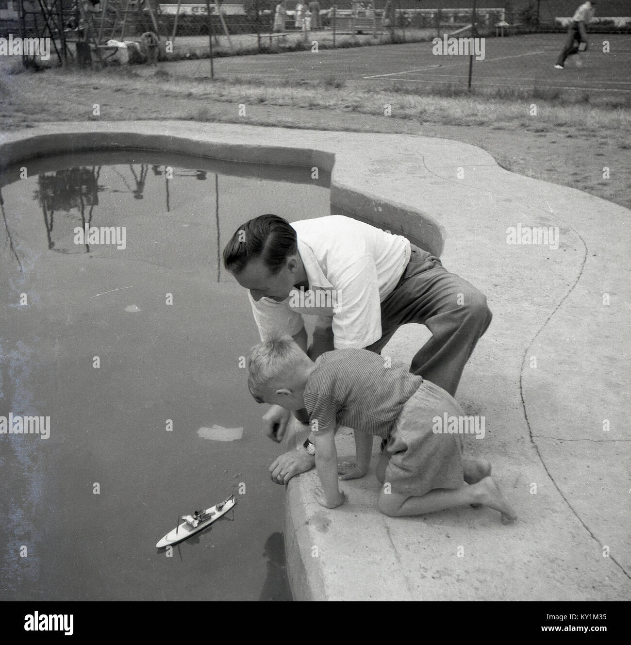 1950s, historical, father with his son playing with his toy boat outdoors at a small boating lake in a park, England, Stock Photo