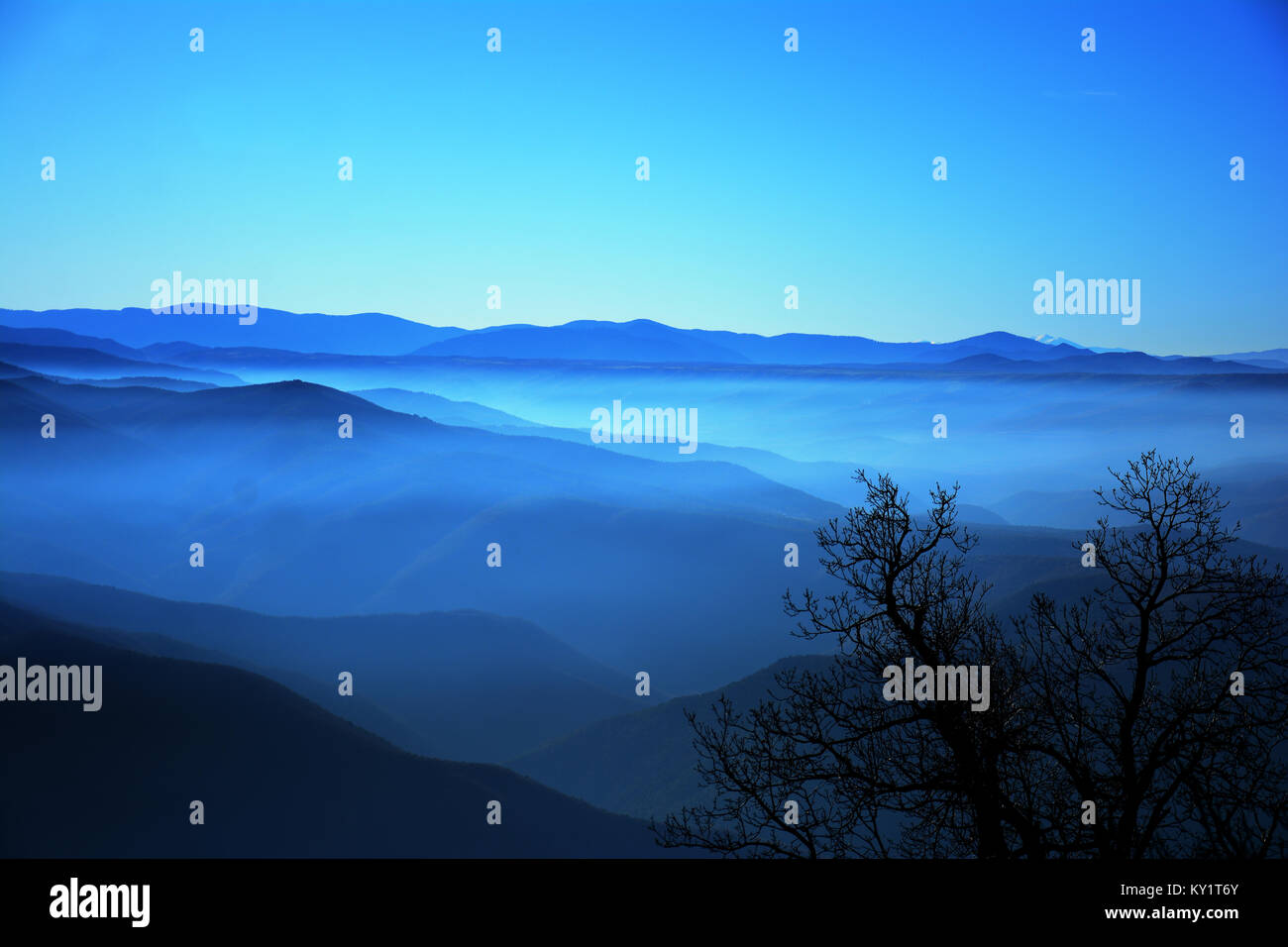 wavy blue mountains and fog - Stock Image