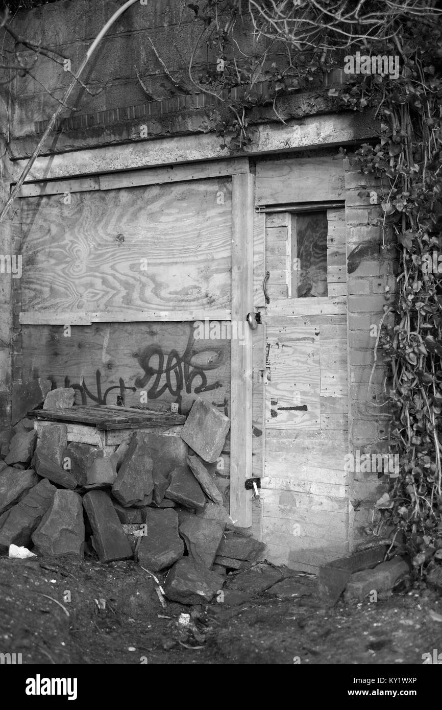 January 2018 - Secure temporary wooden door with big locks to an old building used by squatters. - Stock Image