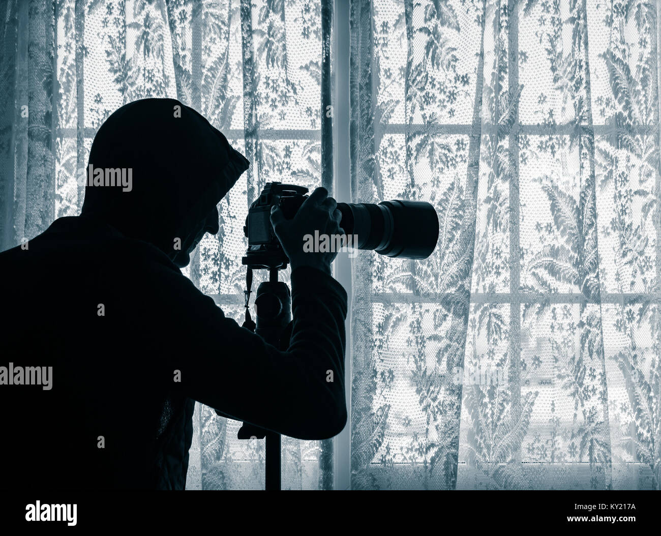 Man wearing hoodie at window looking at LCD screen of camera which has telephoto lens attached. Concept image for - Stock Image