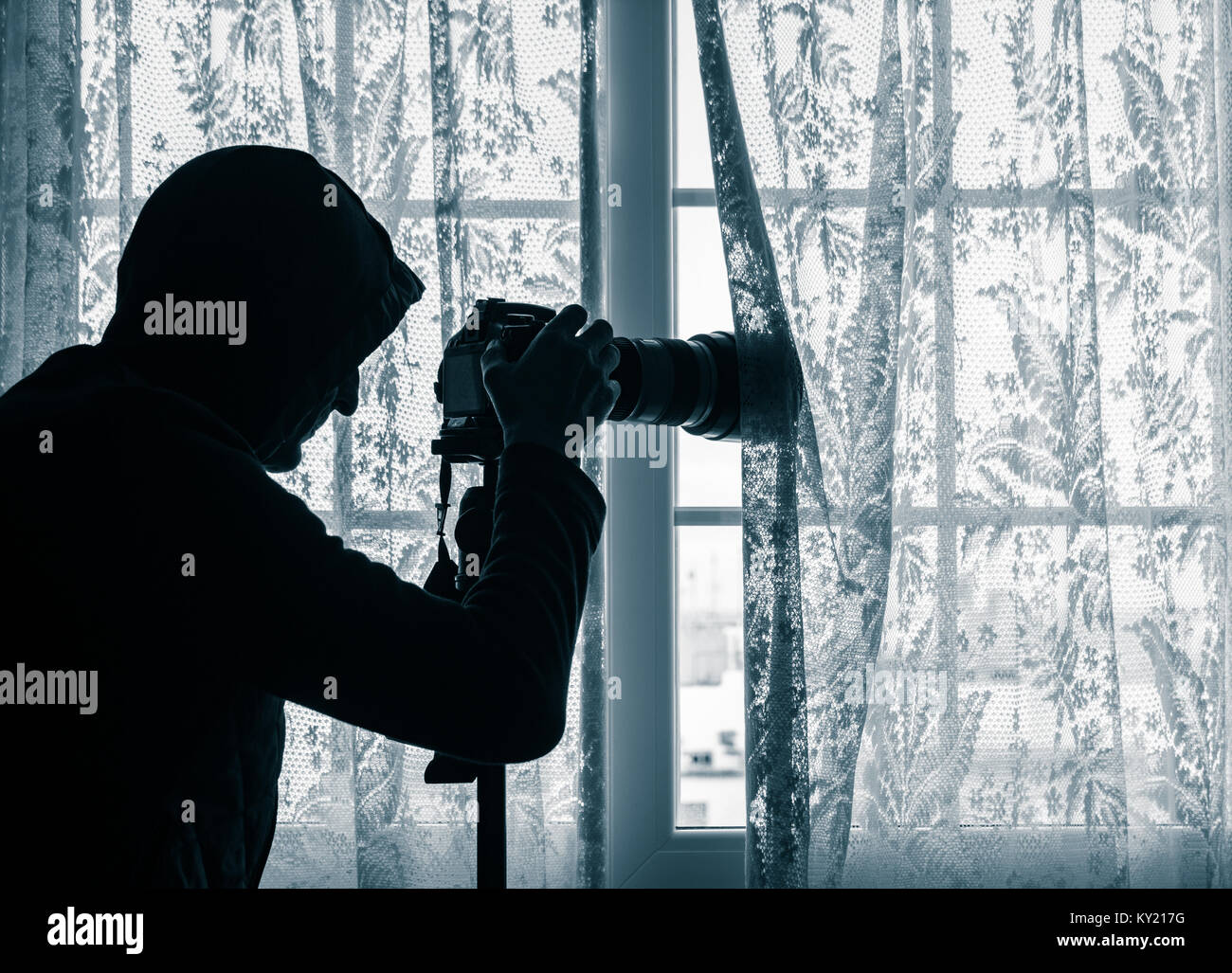 Man wearing hoodie at window looking at LCD screen of camera which has telephoto lens attached. Concept image for Stock Photo